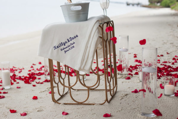 Close up Champagne and Rose Pedals on The Beach | 59&Bluebell Weddings and Events|
